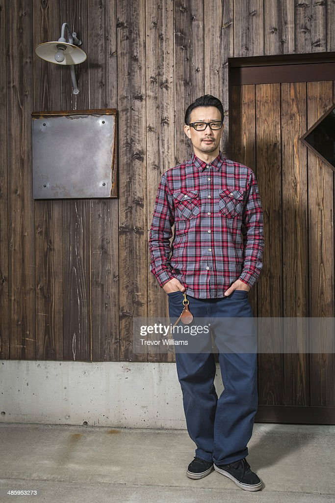 A man standing in front of a wooden building : Stock-Foto