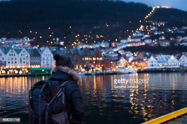 A man standing in front of Bergen havn with traditional wooden buildings in Bryggen in the background