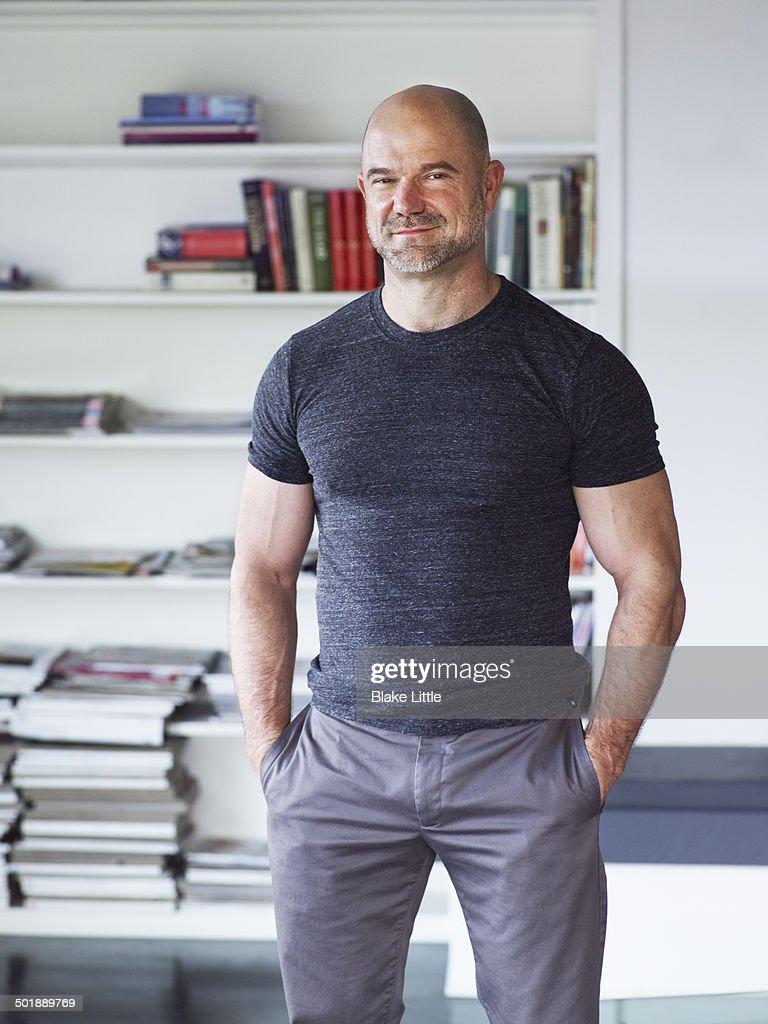 Man standing in front of bookshelf : Stock Photo