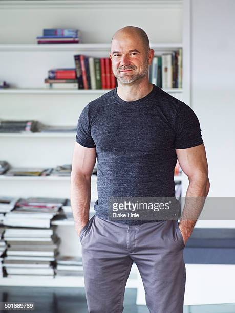 man standing in front of bookshelf - handsome 50 year old men stock photos and pictures