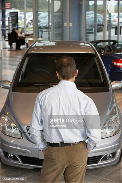 Man standing in front of car in showroom, hands in pockets, rear view
