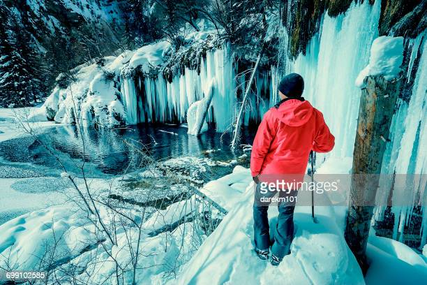 Man standing in front of frozen waterfall, Hanging lake, Colorado, America, USA