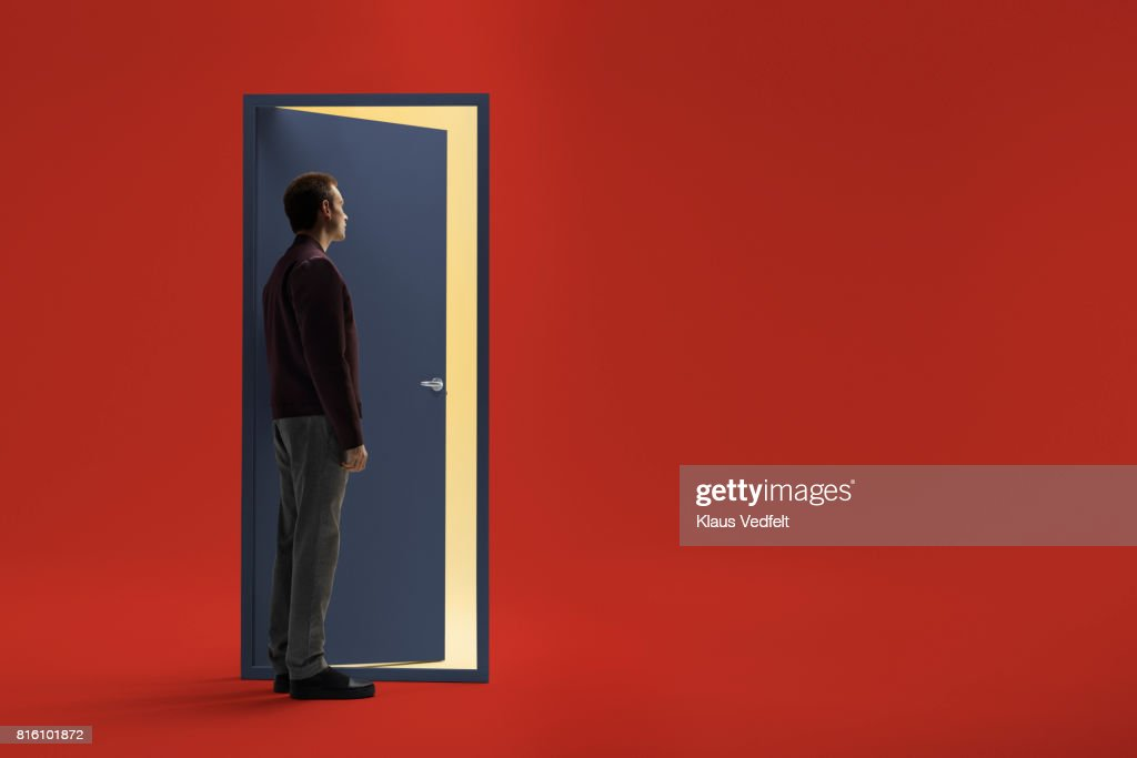 Man Standing In Front Of Half Open Door : Stock Photo