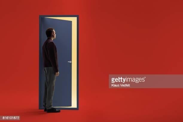 Man standing in front of half open door