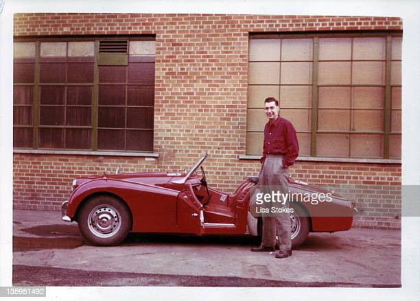 Man standing in front of his red sports car