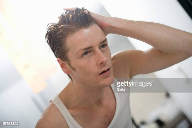 Man standing in front of mirror with hand in hair