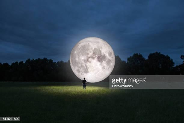 hombre de pie delante de luna - luz de la luna fotografías e imágenes de stock