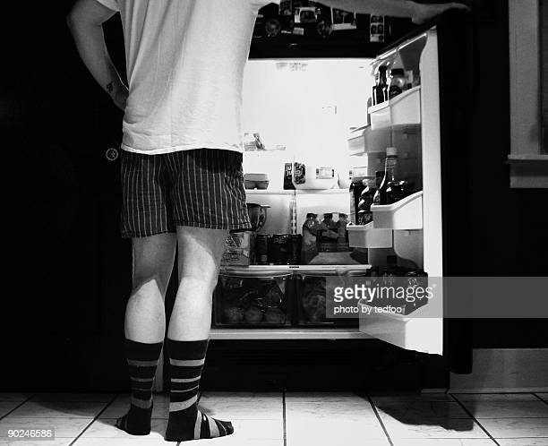man standing in front of open refrigerator - shorts stock pictures, royalty-free photos & images