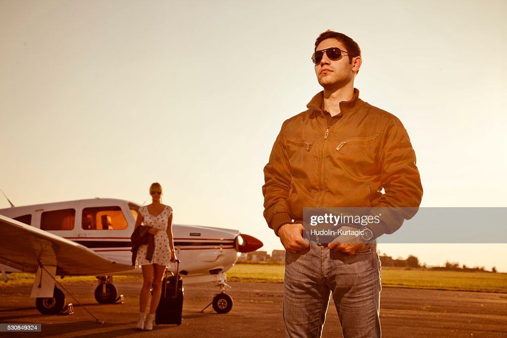 Man standing in front of propeller airplane, woman in background : Stock Photo