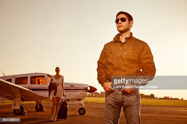 Man standing in front of propeller airplane, woman in background