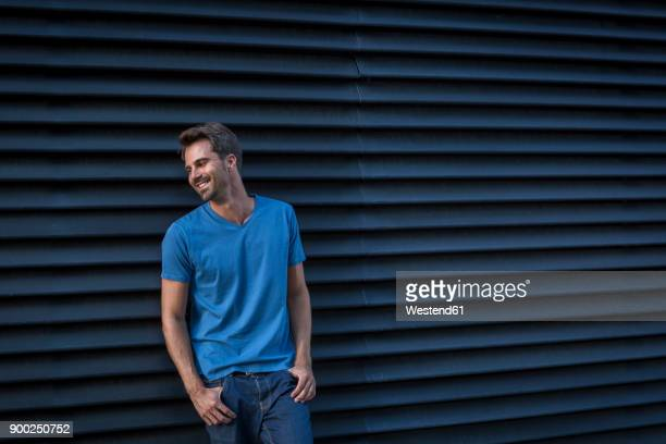 Man standing in front of roller shutter, portrait