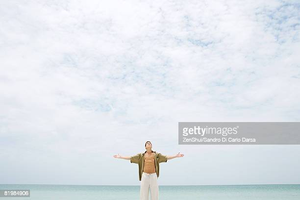 Man standing in front of sea with head back, shirt open, and arms out, mid-distance