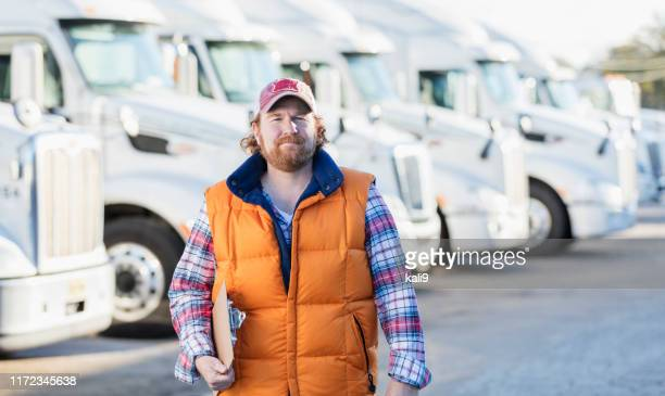 man standing in front of semi-truck fleet - masculinity stock pictures, royalty-free photos & images