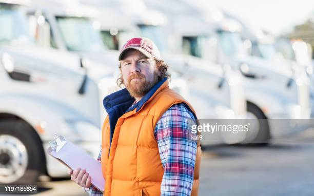 man standing in front of semi-truck fleet - trucker's hat stock pictures, royalty-free photos & images