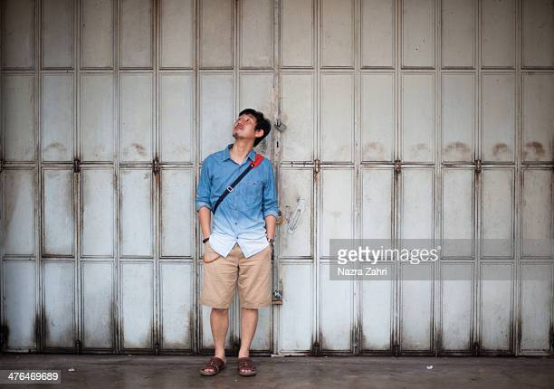 Man standing in front of shophouse shutter