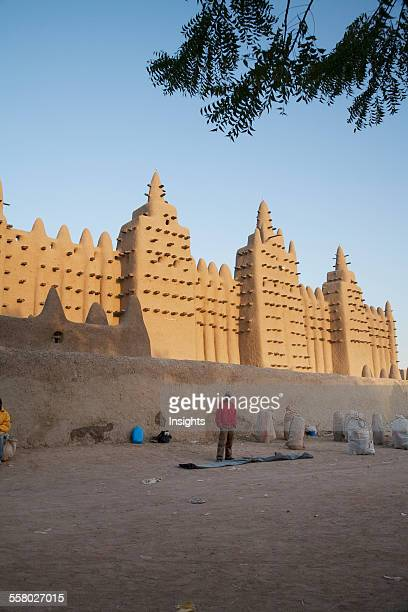 Man Standing In Front Of The Grand Mosque At Djenne Mali