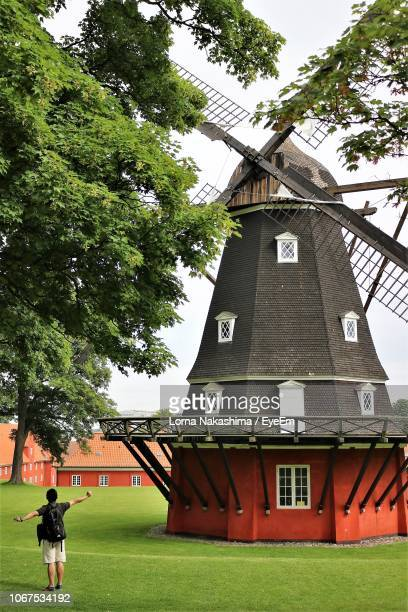 man standing in front of traditional windmill - traditional windmill stock photos and pictures