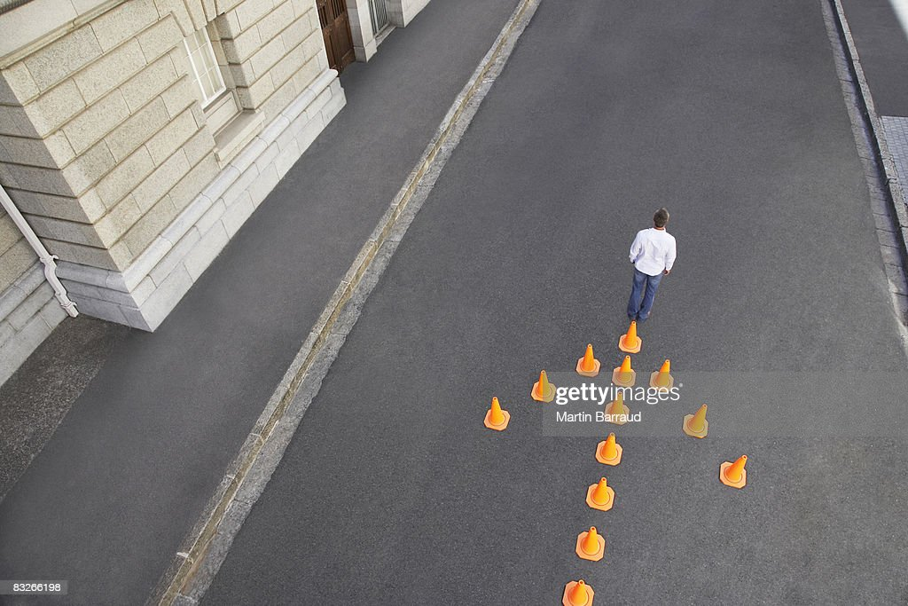 Man standing in front of traffic cones in arrow-shape : Stock Photo