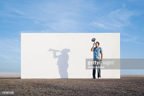 Hombre parado frente a la pared aire libre con megáfono