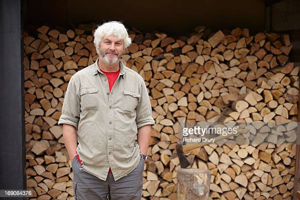 man standing in front of woodshed full of logs - richard drury stock pictures, royalty-free photos & images