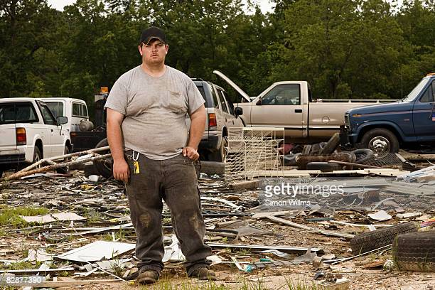 Man standing in front of wrecking yard