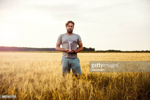 Man standing in grain field holding miniature wind turbine