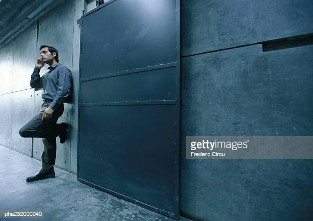 Man standing in hallway on talking cell phone.