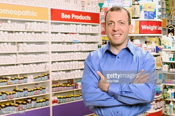 Man standing in health food store, arms crossed, portrait