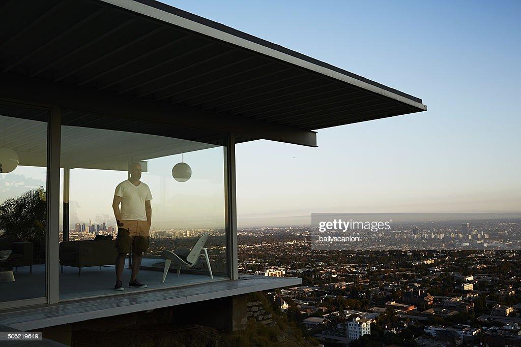 Man Standing In House Overlooking Los Angeles. : Stockfoto