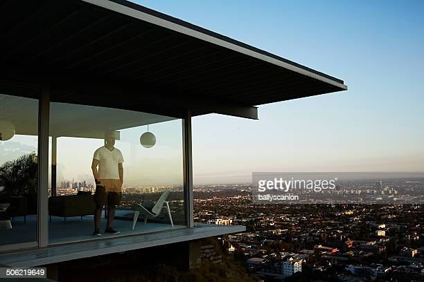 man standing in house overlooking los angeles. - ricchezza foto e immagini stock