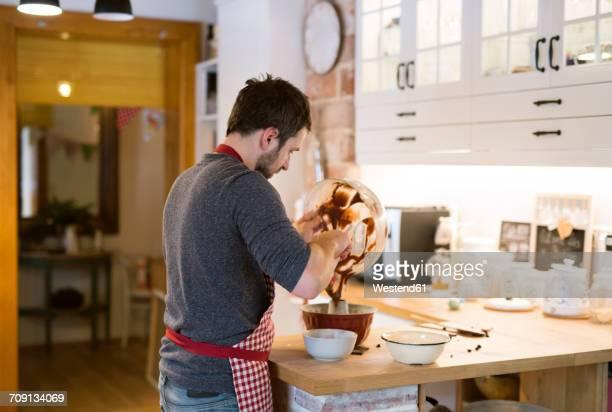 Man standing in kitchen baking ring cake