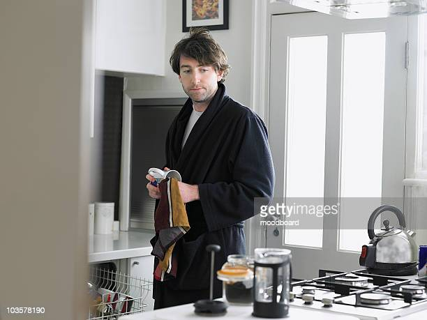 Man standing in kitchen, empting dishwasher