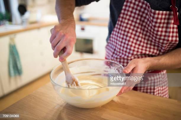 Man standing in kitchen, preparing cake dough