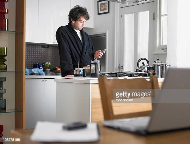 man standing in kitchen, text messaging, laptop on table in foreground - bathrobe stock pictures, royalty-free photos & images