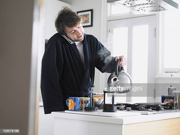Man standing in kitchen using phone, pouring water into coffee plunger