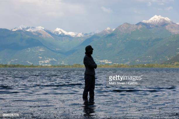 Man Standing In Lake Against Mountains