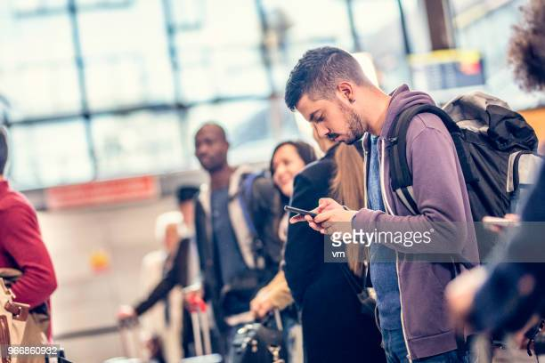 Man standing in line at an airport using a smart phone