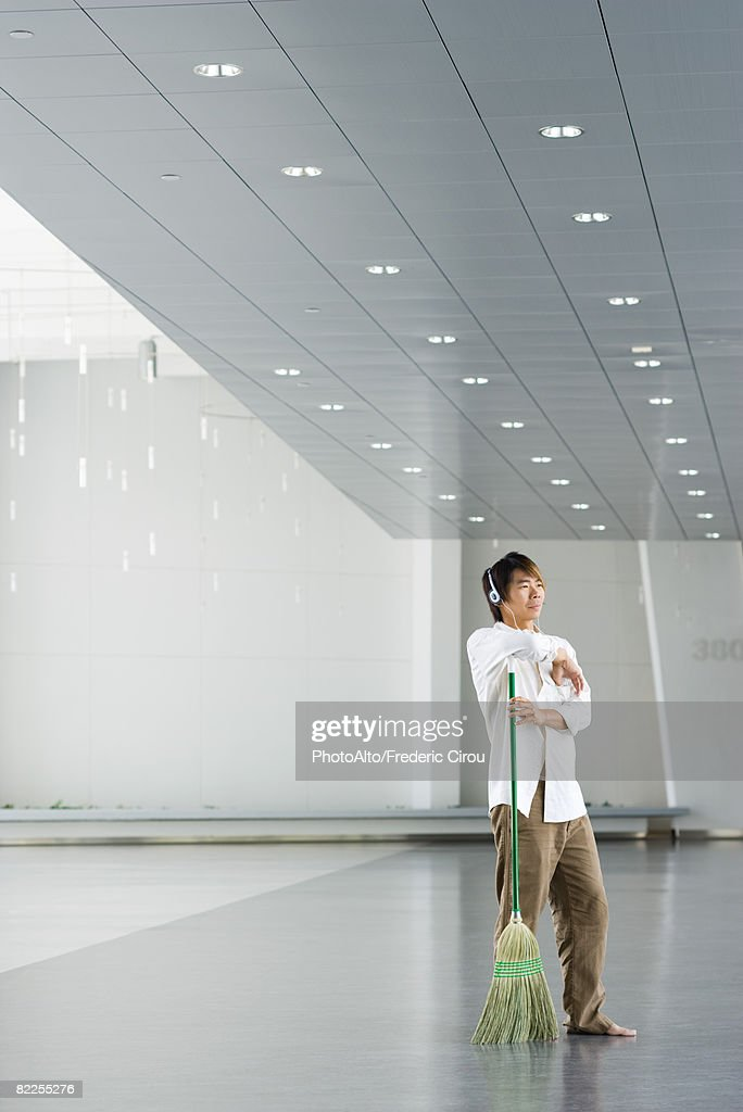 Man standing in lobby, resting arm on broom, listening to headphones : Stock Photo