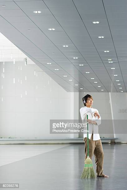 Man standing in lobby, resting arm on broom, listening to headphones