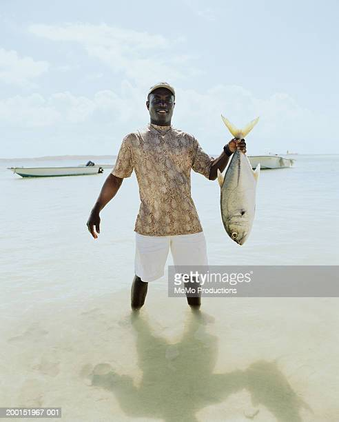 man standing in ocean holding fish, portrait - catching stock pictures, royalty-free photos & images