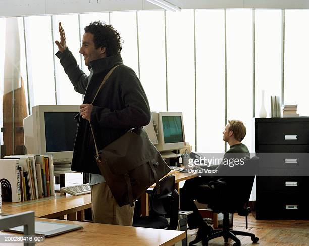 man standing in office carrying shoulder bag, hand raised - ankunft stock-fotos und bilder