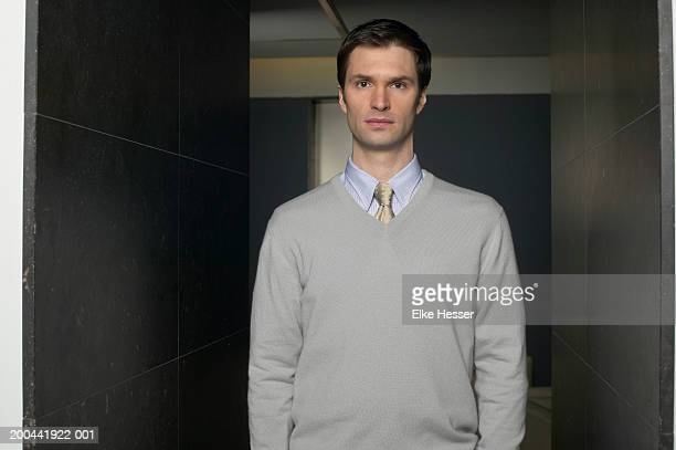 man standing in office corridor, arms by sides, portrait - v neck stock pictures, royalty-free photos & images