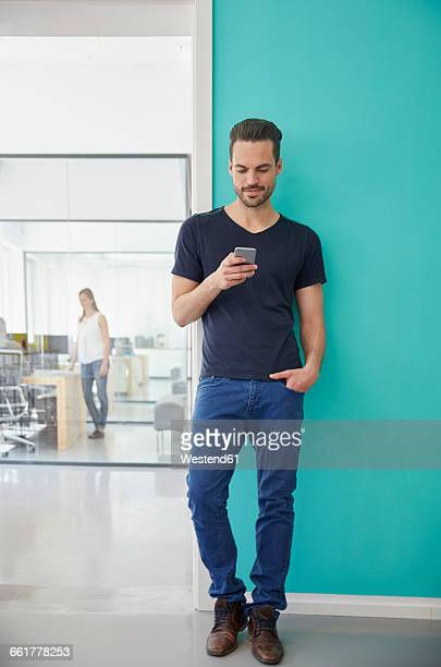 man standing in office using smart phone - leuchtende farbe stock-fotos und bilder