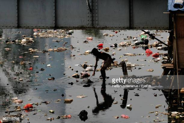 man standing in polluted water - water pollution stock pictures, royalty-free photos & images