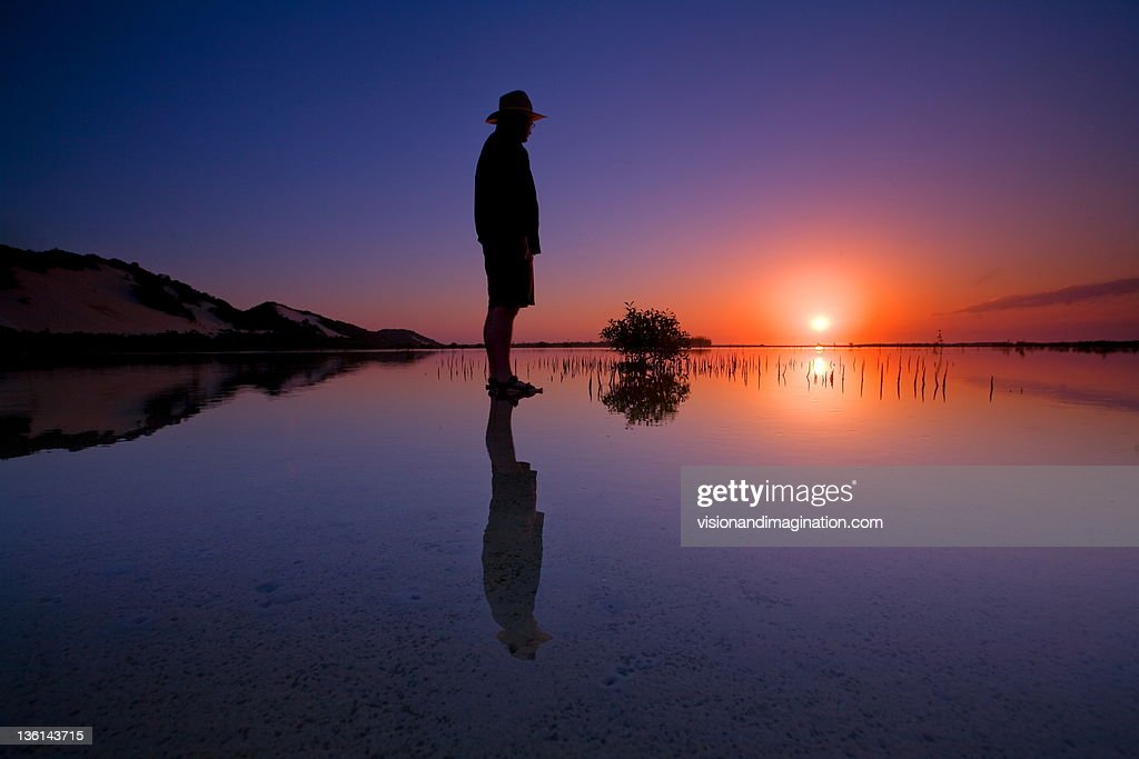 Man standing in river at sunset : Stock Photo