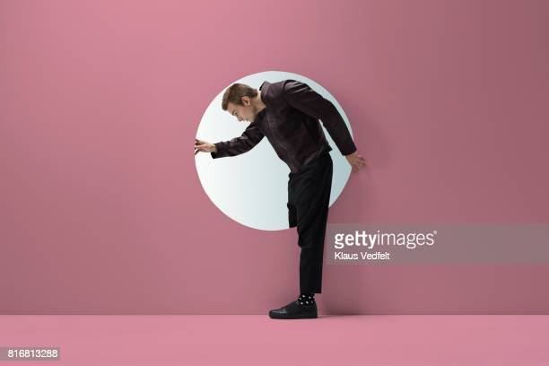 Man standing in round opening in coloured wall