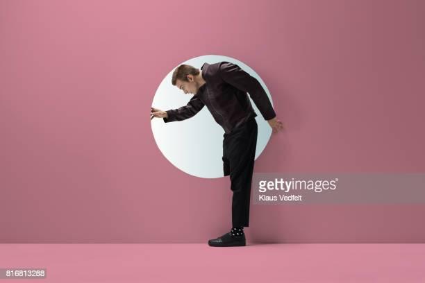 man standing in round opening in coloured wall - beugen oder biegen stock-fotos und bilder