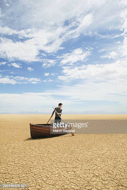 man standing in row boat on cracked earth - sin esperanza fotografías e imágenes de stock