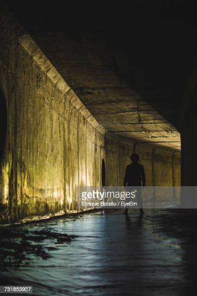 Man Standing In Sewage Tunnel
