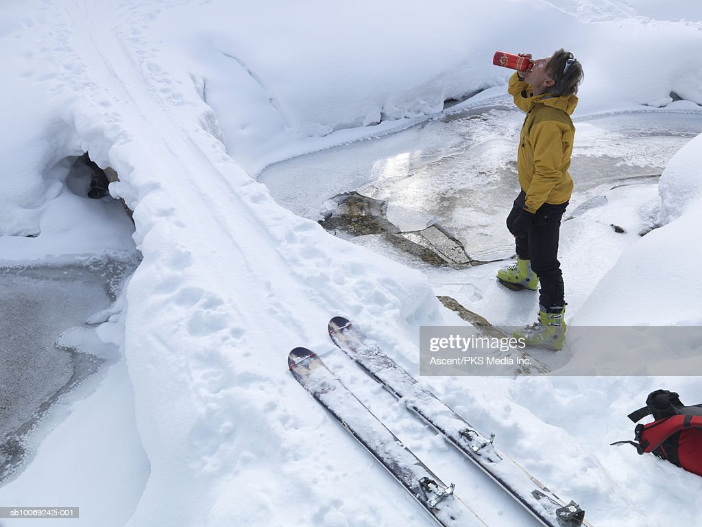 Man standing in snow drinking water from bottle, side view : Stockfoto